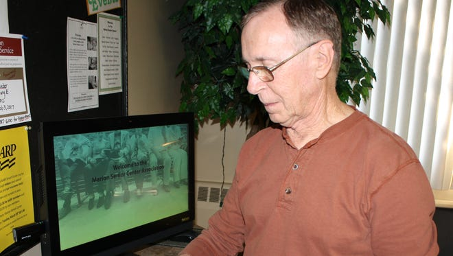Steve Renick, a Tai Chi instructor at the Marion Senior Center and a member, demonstrates the new check-in system.