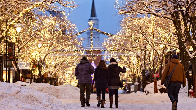 Pedestrians walk on a freshly snow-covered Church Street Marketplace in Burlington on Tuesday evening, Dec. 12, 2017, following the first significant snowfall of the season.
