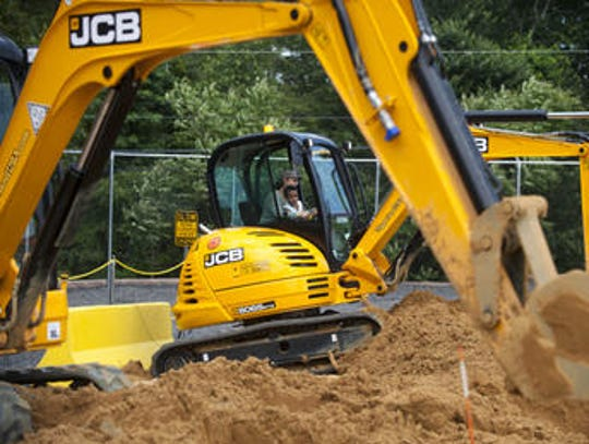 Visitors dig with a giant excavator at Diggerland in