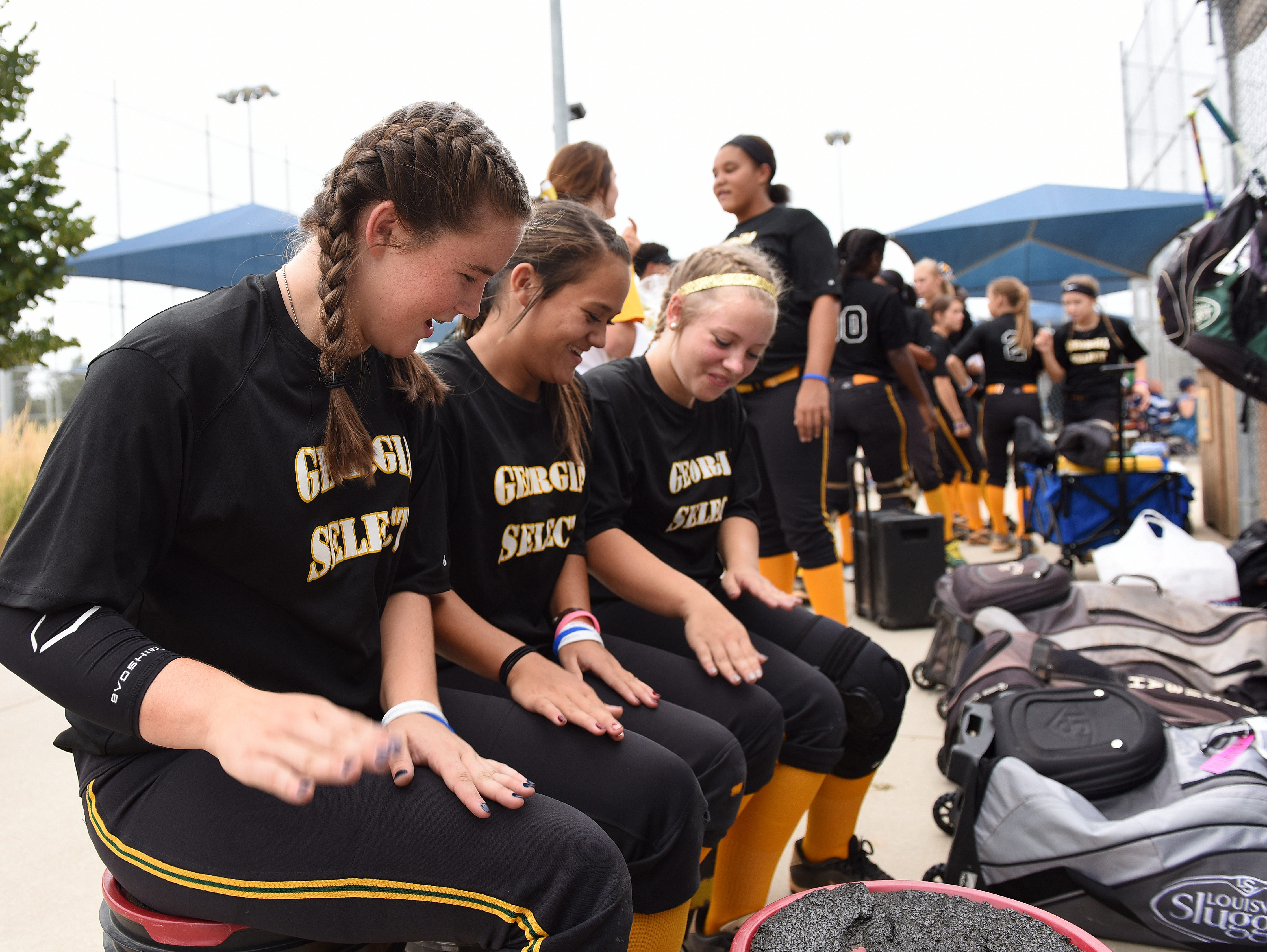 George Select's Madyson Coe, Faith Barth and London Berkhiser chant before they play during the ASA 14U national softball tournament at Sherman Park in Sioux Falls, S.D., Monday, Aug. 1, 2016.