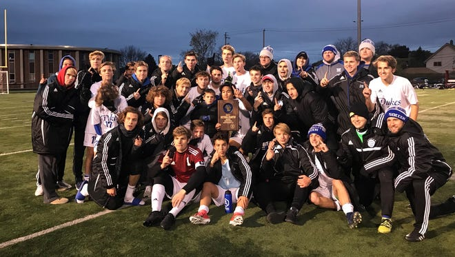 Whitefish Bay's boys soccer team poses with the sectional championship plaque after a 4-0 win over Brookfield Central at Shorewood High School on Oct. 28.