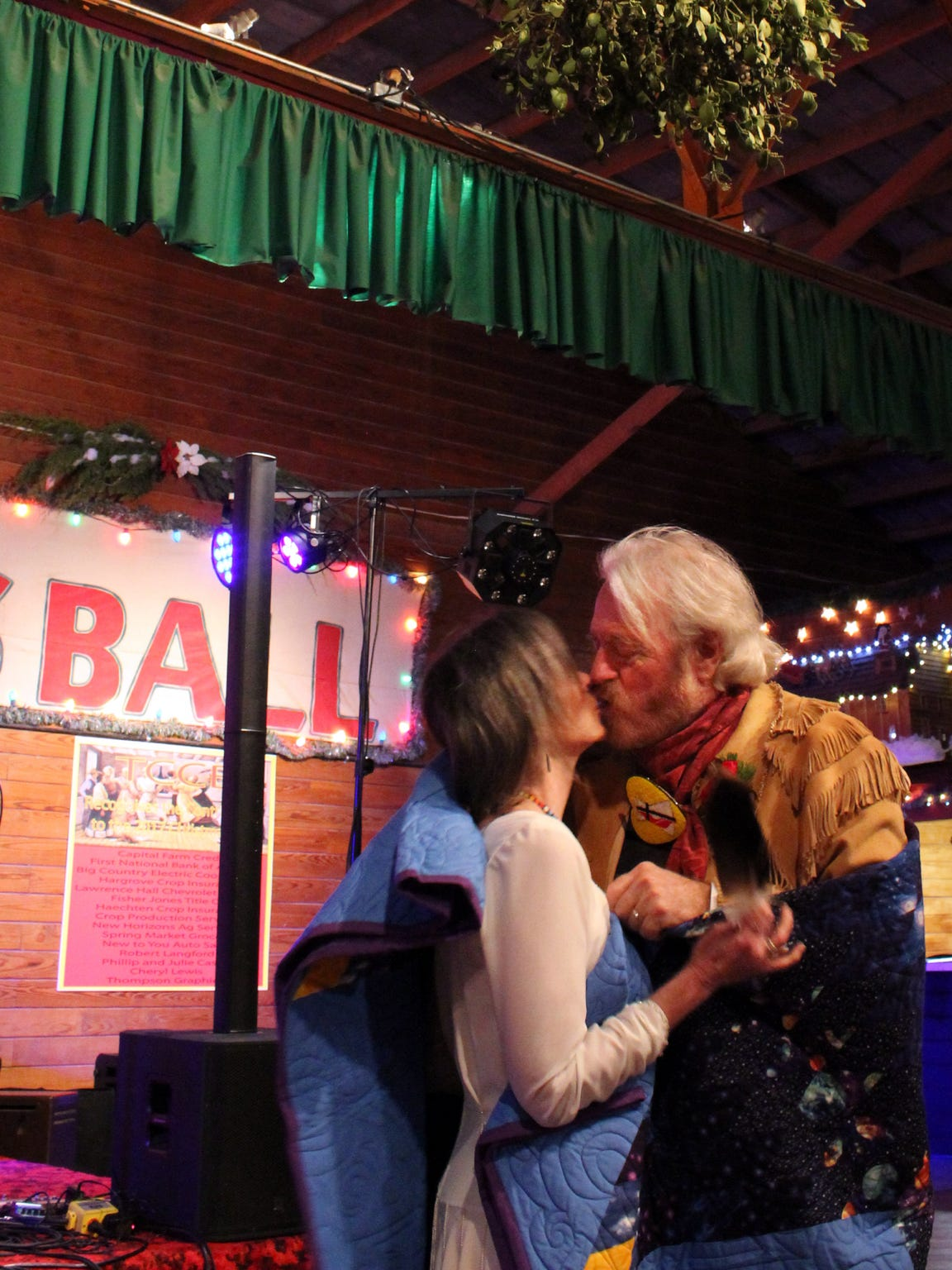 Newlyweds Cynthia Tune and Michael Martin Murphey kiss, several times, under the mistletoe at Pioneer Hall in Anson, where they married Dec. 16.