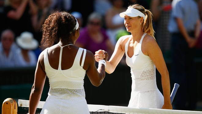Serena Williams celebrates at the net after winning a match against Maria Sharapova during the Wimbledon Lawn Tennis Championships at the All England Lawn Tennis and Croquet Club on July 9, 2015.