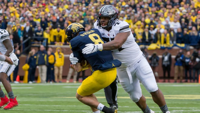 Ohio State defensive tackle Michael Hill tackles Michigan quarterback John O'Korn in the second half.