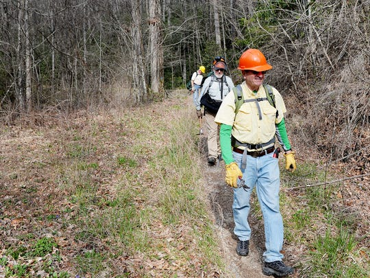 Craig Smith walks along Davidson River Trail April 3, 2018 with members of the Pisgah Trail Crew, a Forest Service volunteer group.