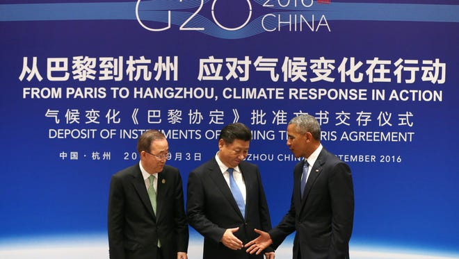 This Sept. 2, 2016, file photo shows Chinese President Xi Jinping, center, former president Barack Obama and former UN Secretary General Ban Ki-moon shaking hands during a joint ratification of the Paris climate agreement in Hangzhou.