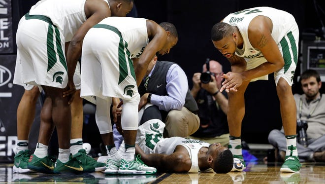Michigan State teammates surround guard Eron Harris after he was injured Saturday.