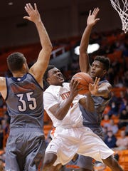 UTEP's Lee Moore goes to the basket between University of Texas-Rio Grande Valley defenders Dakota Slaughter (35), left, and Adonis Rwabigwi (32), right, in the first half of their game Tuesday at the Don Haskins Center.