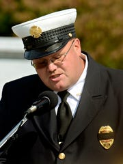 Fire Chief Ira Walker reads the Fireman's Prayer during