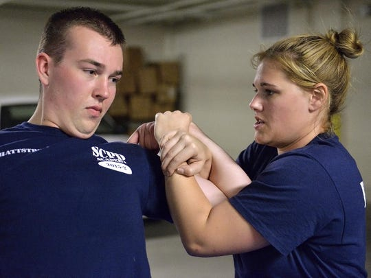 St. Cloud Police Department recruit Brittany Peterson, right, puts partner Alex Hattstrom in a hold Tuesday during training.