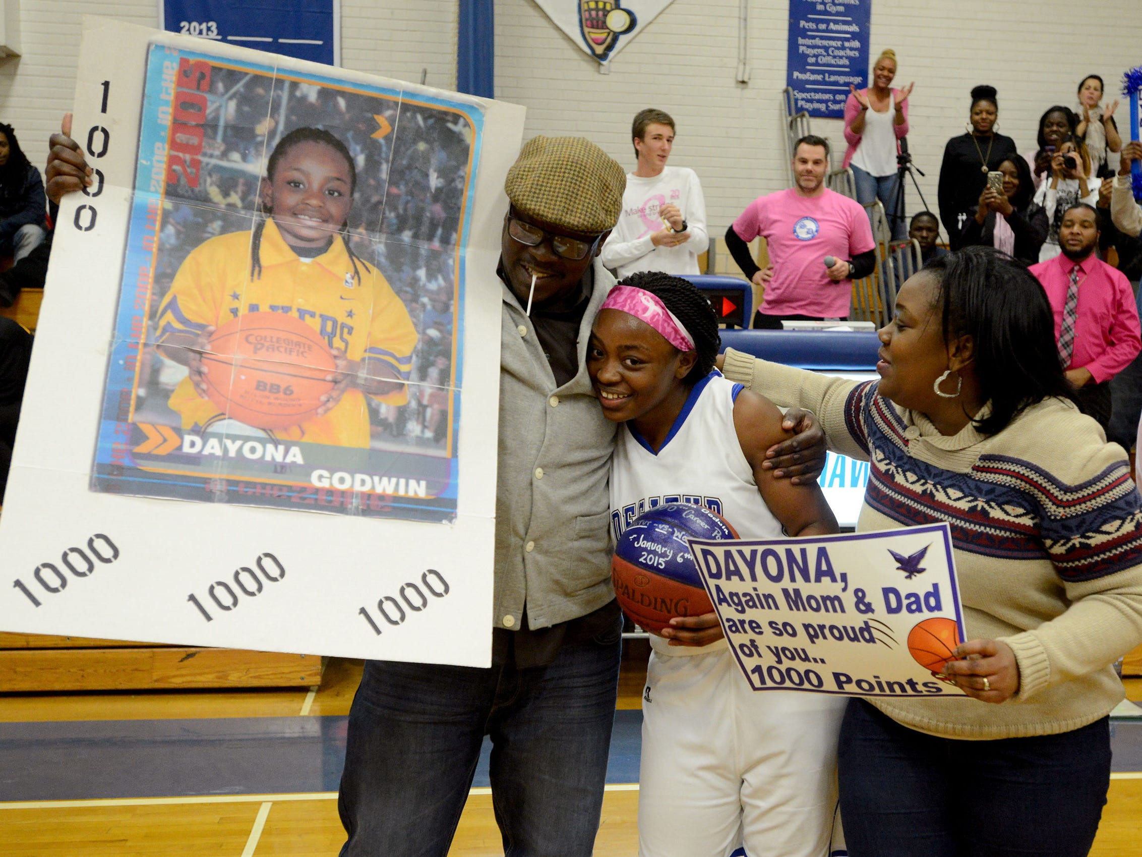 Stephen Decatur's Dayona Godwin gets a celebratory hug from her father, Derek Godwin, left, and her mother Natasha Brittingham after scoring her 1,000th point Tuesday evening.