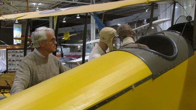 """Glenn H. Curtiss Museum of Aviation History Executive Director Trafford Doherty looks over the shoulder of two """"pilots"""" studying the controls of one of the many airplane exhibits at the museum in Hammondsport."""