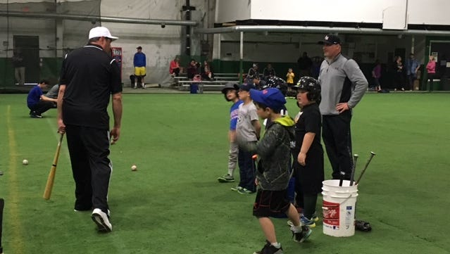 Coaches at the Edge work with young students during a baseball camp.