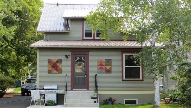 """The back of John Wocken's home in the Lake George Neighborhood features decorative """"barn quilts."""""""