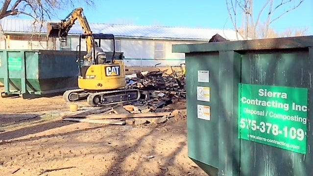 Debris from the burned home is loaded into a roll-off to be hauled to Sierra Contracting.