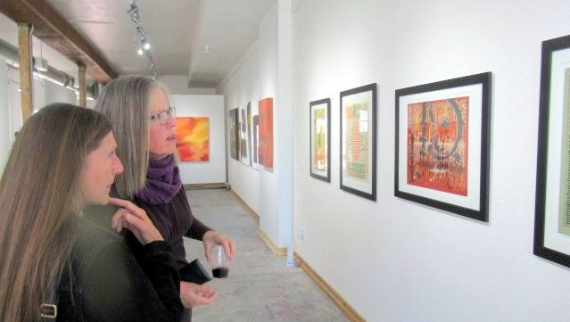 Two patrons view the artwork in Limina Art Gallery during its grand opening Sunday in Carrizozo.