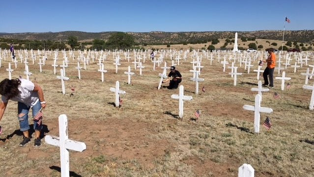 Volunteers turned out last year to help place flags at each grave in the military cemetery at Fort Stanton.