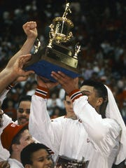 Ball State players celebrate with the 1990 Mid-American Conference Tournament trophy.