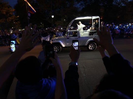 Those waiting along Logan Square pulled out their phones to take a photo of Pope Francis as he drove by on the way to the festival on the parkway.