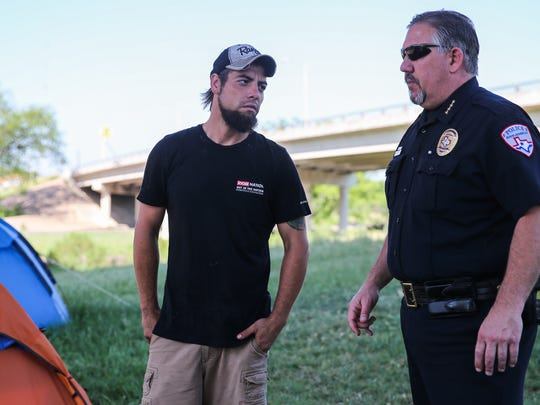 Dustin Halvorson talks to Police Chief Frank Carter at tent city under the Houston Harte Expressway in San Angelo.
