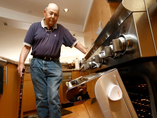 Bill Dworsky, 81, shows off the Lively activity sensor attached to the side of the oven door at his home on May 16, 2014 in San Francisco, Calif. Small, multiple sensors installed in key places in his home, monitors he and his wife's activity, so their son can keep a passive eye on them to make sure they are safe.