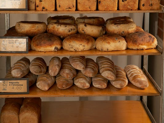 Rack with loaves of bread in bakery