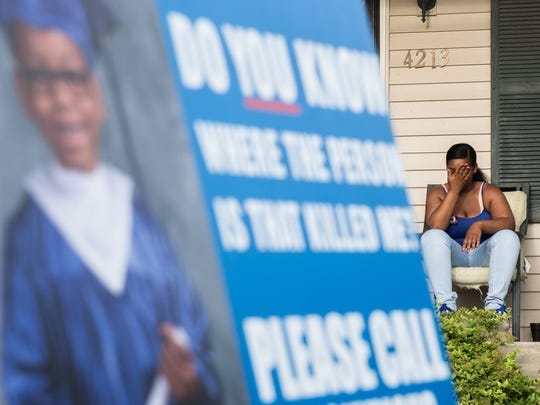"Micheshia Norment has placed ""Do you know where the person is that killed me?"" signs all over Louisville. Here, she sits on her cousin's porch on July 4, which was Dequante's favorite holiday. July 4, 2017."