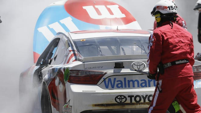 Safety crews extinguish the fire on Kyle Busch's car in the garage during the race at MIS on Sunday, June 12, 2016