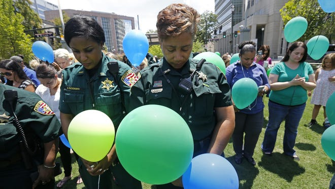 East Baton Rouge Sheriff's deputies Natasha Stingley, right, and Minnie Ducksworth, left, bow their heads in prayer before releasing balloons at a noon vigil organized by municipal court workers in downtown Baton Rouge, La., Wednesday, July 20, 2016, in honor of recent slain and injured sheriff deputies and police.