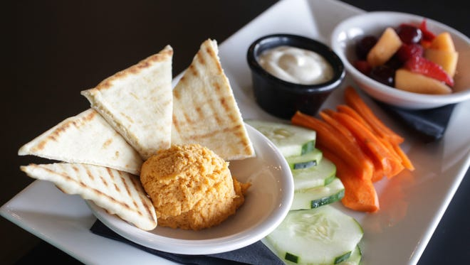 The Pure Fresh Plate with hummus, homemade dressing, carrots, cucumbers, fresh fruit and warmed pita.