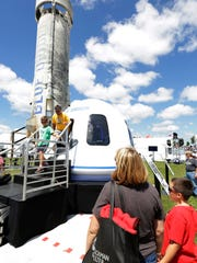 Daniel Farias and son Diego Farias of Avon, Indiana, exit the crew capsule of the Blue Origin rocket at EAA AirVenture in Oshkosh.