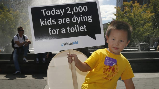 A boy with the international organization WaterAid helped in a rally Sunday for increasing access to sanitation and safe drinking water.
