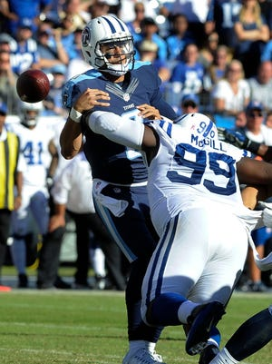 Colts defensive tackle T.Y. McGill (99) knocks the ball out of Titans quarterback Marcus Mariota (8) hands late in the fourth quarter Sunday.