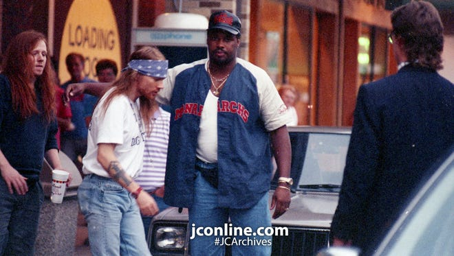 Axl Rose and unidentified companions are escorted from Arni's Restaurant in Lafayette's Market Square Shopping Center. Photo taken July 23, 1992.