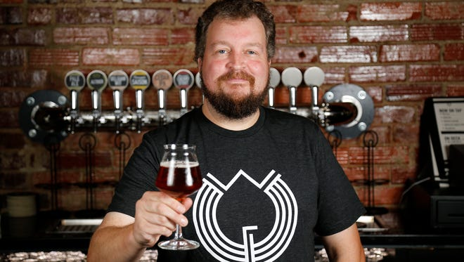 Co-owner Chris Mitchell poses behind the bar at Woodburn Brewery in East Walnut Hills.