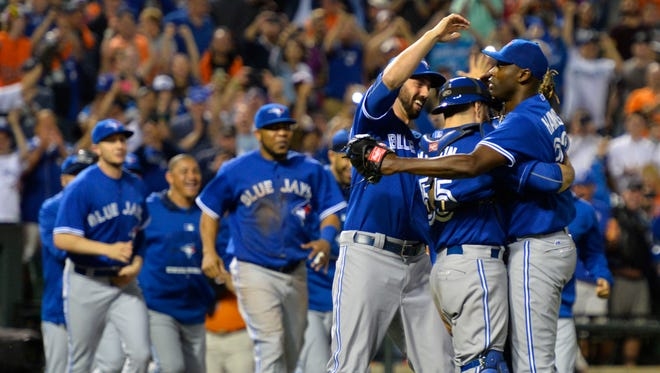 The Blue Jays celebrate on the field after clinching the AL East.