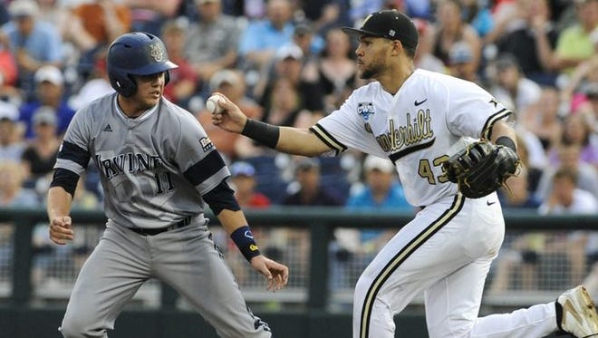 UC Irvine's Jerry McClanahan, left, is tagged out by Vanderbilt first baseman Zander Wiel, right, between first and second base after he was caught stealing in the third inning Monday.