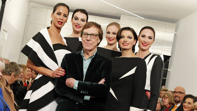 Models pose with Dutch fashion designer Frans Molenaar during the presentation of his spring/summer 2013 collection in Amsterdam, on March 17, 2013.