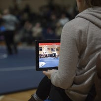 Collingwood sophomore and wrestllng manager Carly Gregg records the team's Feb. 1 match on an iPad from the bench at Gateway. Video remains an essential technology in the sport.