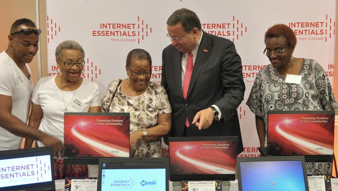 David Cohen, a senior executive vice president of Comcast, center, explains the company's Internet Essentials program to seniors at the Mary V. McDonald Wilson Center in Palm Beach County, Fla., in 2015, when the program was launched there.