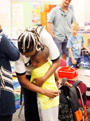 Zion Wright hugs his mother, Jammie, as she drops him off in his classroom for the first day of school at Vance Elementary in West Asheville  in 2016.