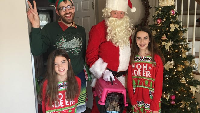 Volunteers from St. Hubert's dressed as Santa Claus and an elf deliver a shelter cat, named Mittens, to the Geary family in Hanover on Christmas morning, Dec. 25, 2017.