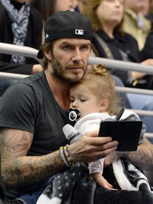 Soccer player David Beckham with daughter Harper as they watch the game between the Calgary Flames and Los Angeles Kings at the Staples Center.