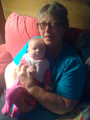 Breast Cancer survivor Pamela Banks holds her 2-month-old great granddaughter, Savannah, on Sept. 30. Banks is doing so well, she and her husband now provide full-time day care for Savannah.