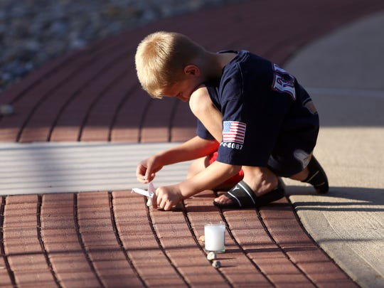 7-year-old Kaiden Reed of Mendham places a stone in remembrance on the brick naming his fathers uncle, Donald Burns of the FDNY during the Morris County September 11th remembrance service and candlelight vigil at the Morris 9/11 Memorial. September 11, 2016, Parsippany, NJ