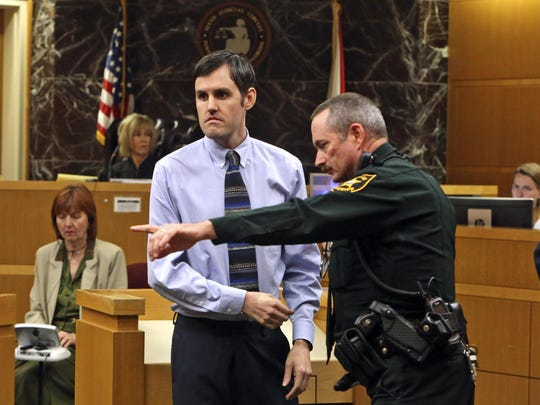 Defendant John Jonchuck is directed by a Pinellas County Sheriff deputy to the finger print area after a jury found him guilty, Tuesday, April 16, 2019, Clearwater, Fla. Jonchuck was found guilty of first-degree murder for dropping his 5-year-old daughter off a bridge four years ago, despite arguments from his attorneys that he was insane and thought his actions would actually save her. He was automatically sentenced to life in prison. (Scott Keeler/Tampa Bay Times via AP, Pool)