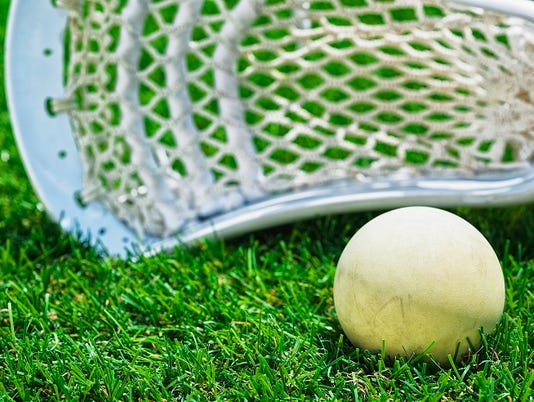 White ball and white Lacrosse stick on artificial turf