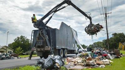 Work crews clear debris from the roadside along La. 92 on Monday.