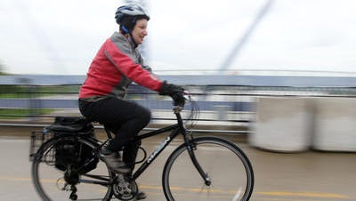 Yiscah Bracha rides her bike across the Purple People Bridge after attending a Bicycle Breakfast at the Bridge, Newport. She works at Cincinnati Children's Hospital and rides to Fountain Square every day to catch a bus.