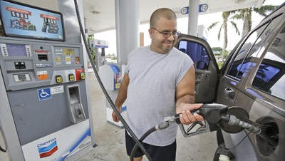 In this Wednesday, June 4, 2014 photo, Baltazar Rosado, of Hollywood, Fla., pumps gasoline into his car at a Chevron gasoline station in Pembroke Pines, Fla. U.S. consumer prices rose in June at a slightly slower pace than in May with two-thirds of the June advance driven by the largest jump in gasoline prices in a year.